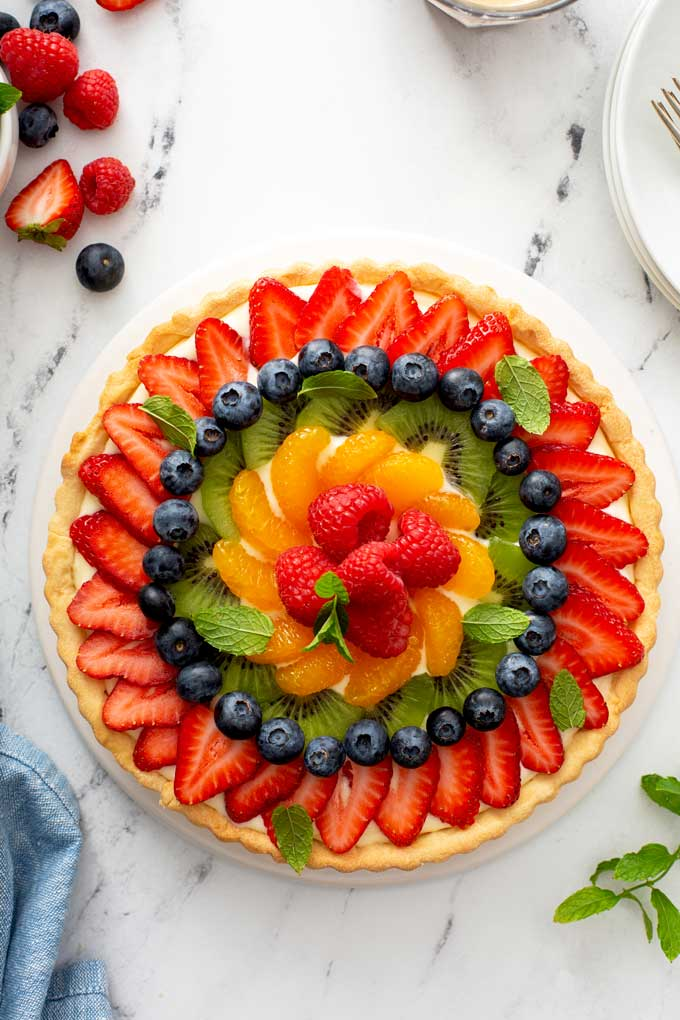 A French Fresh Fruit Tart with strawberries, kiwi, mandarin oranges, raspberries and blueberries on a white platter.