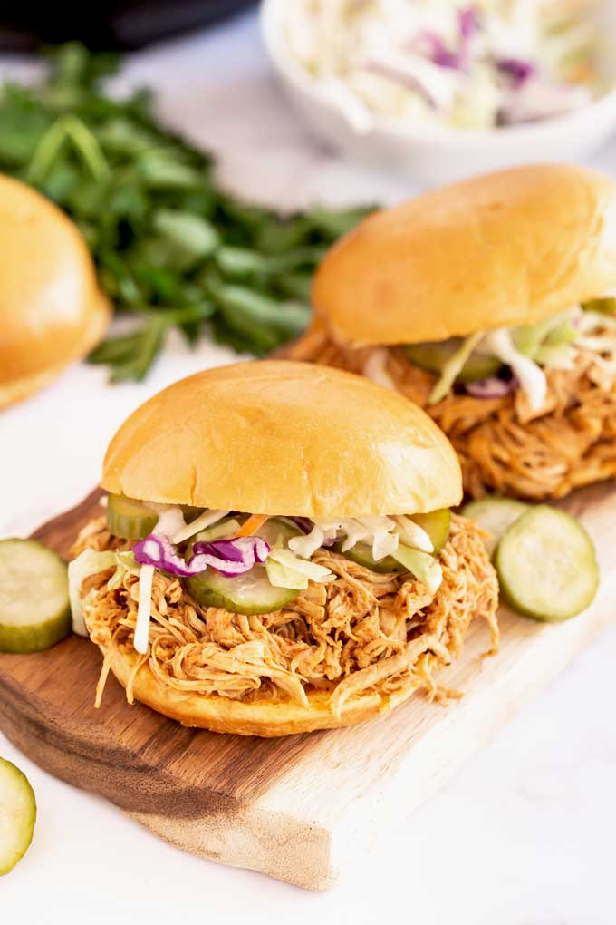 A BBQ pulled chicken sandwich with pickles and coleslaw on a wooden board.