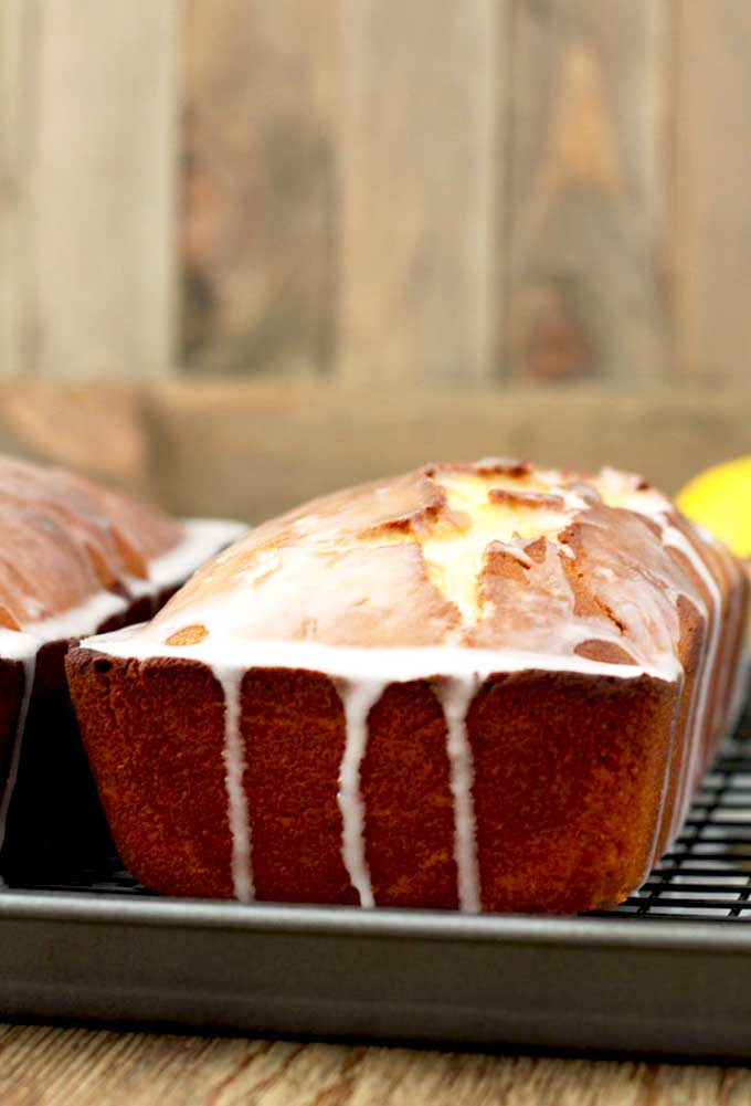 A loaf of lemon bread with lemon glaze on a cooling rack