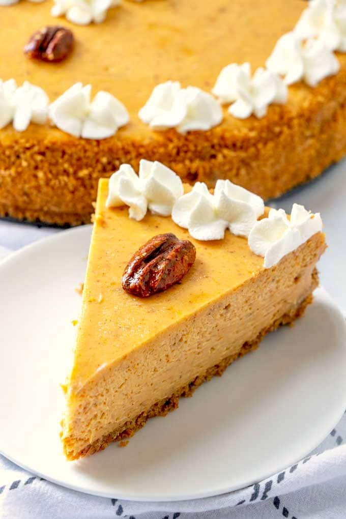 A sliced of pumpkin cheesecake with a pecan on top and whipped cream