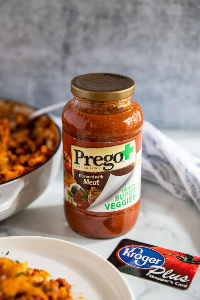 A jar of Prego Hidden Super Veggies flavored with meat and a Kroger's car on a white counter.