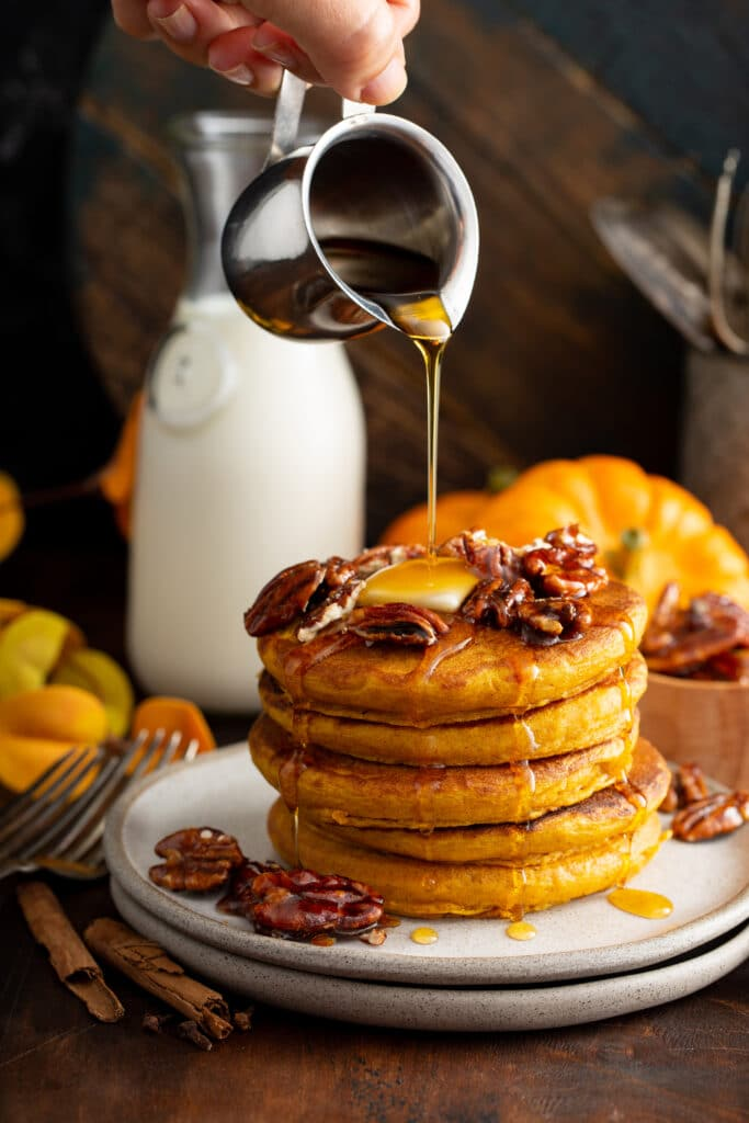 Maple syrup poured over a stack of pumpkin pancakes topped with pecans.