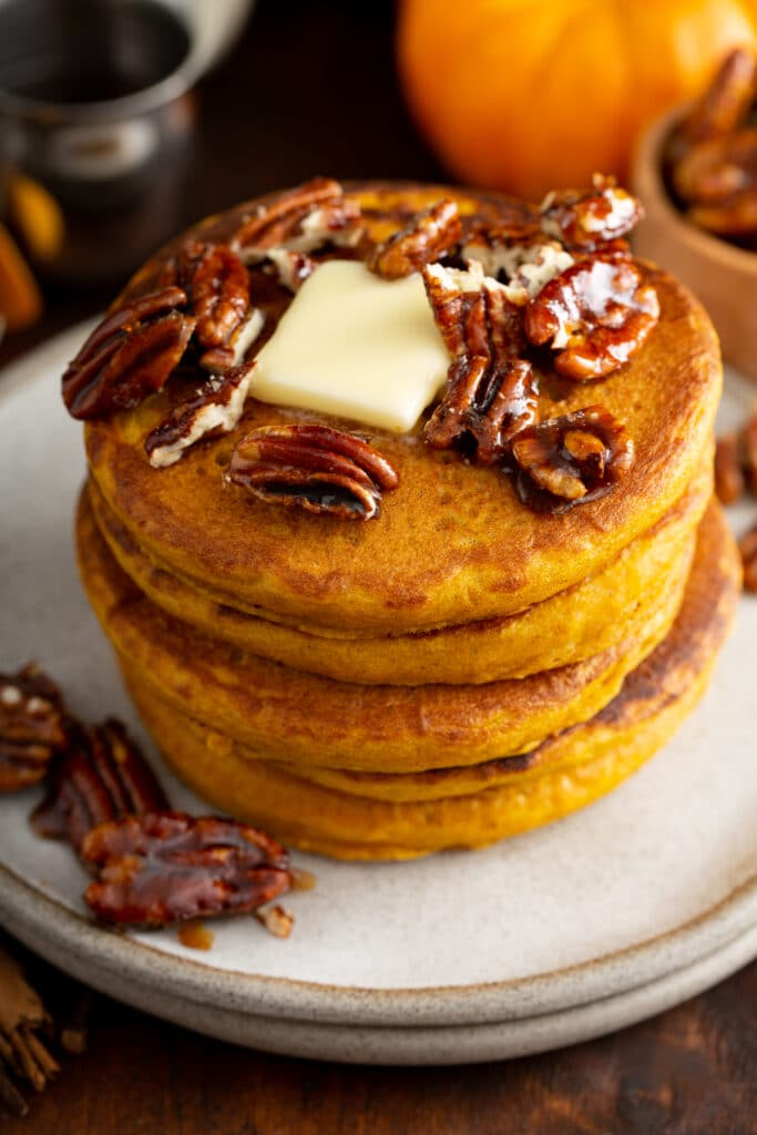 A stack of pumpkin pancakes topped with butter and candied pecans on a white plate,