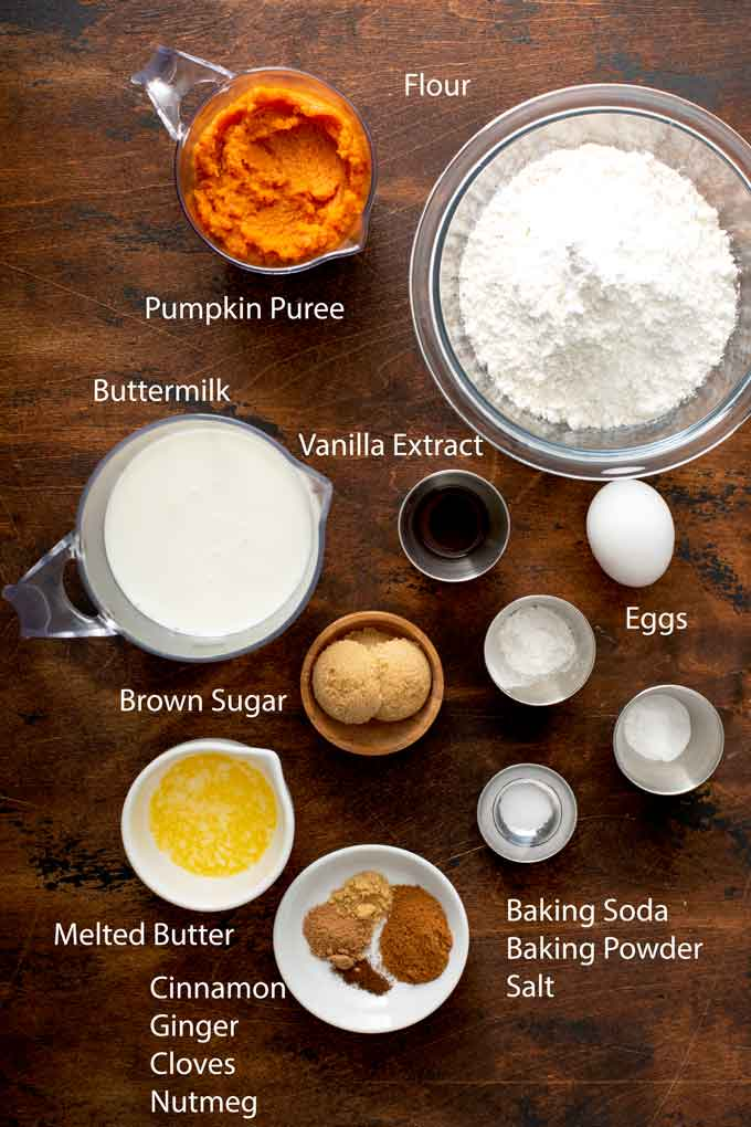 Ingredients to make pumpkin pancakes on a wooden surface.