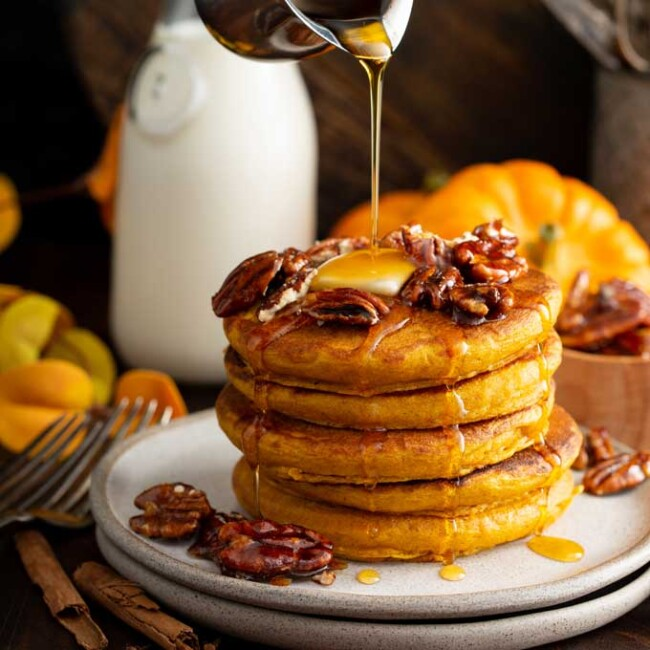 Stack of pumpkin pancakes drizzled with warm maple syrup