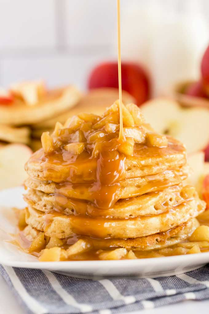 A stack of apple pancakes topped with caramel apples and drizzled with sweet caramel on a white plate