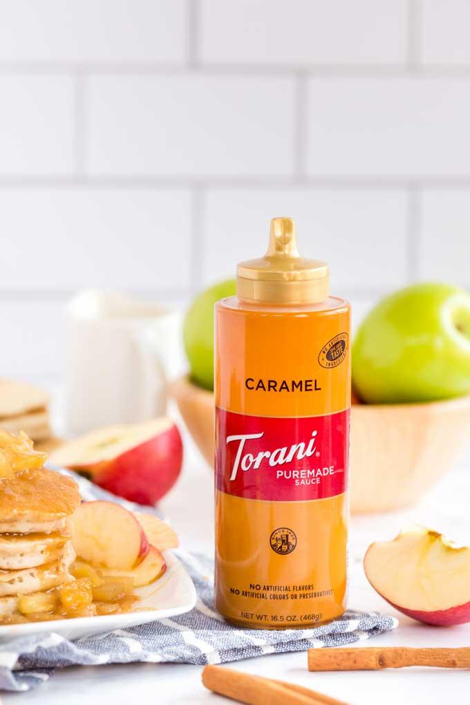 A bottle of Torani Caramel Sauce next to apples, cinnamon and pancakes.