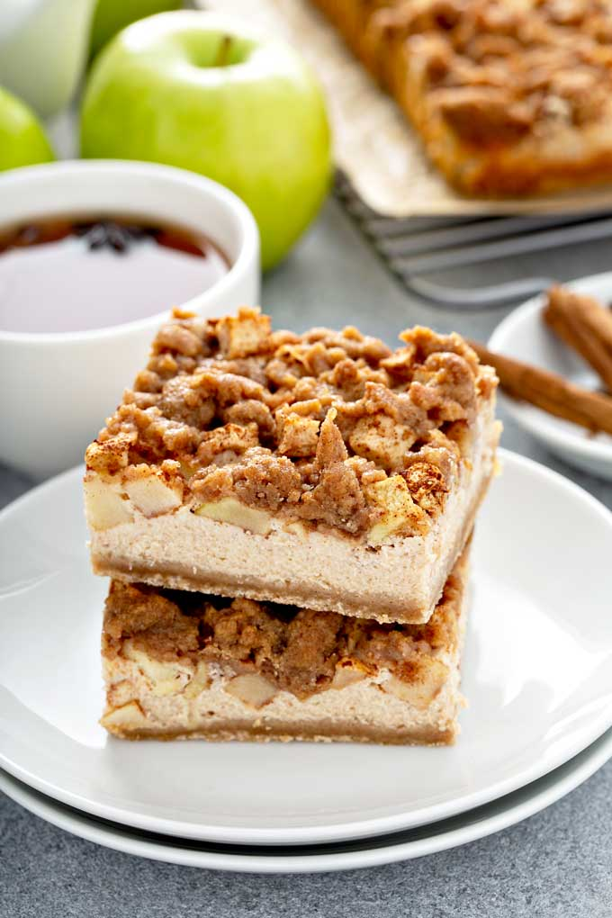 One apple cheesecake bars stacked on top of another on a white plate.