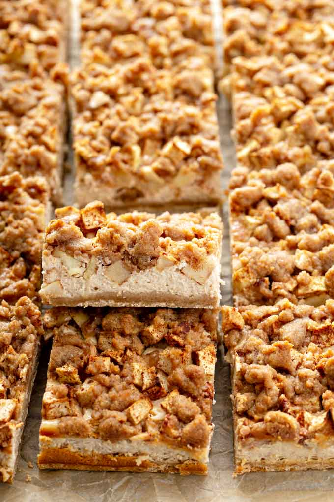 Cheesecake bars cut into squares on a parchment paper.