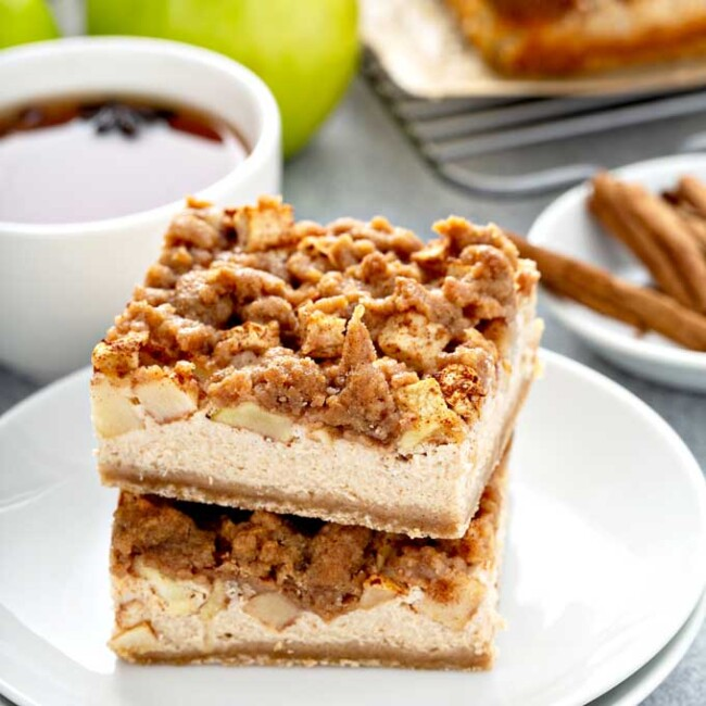 Stack of two apple cheesecake bars on a white plate.