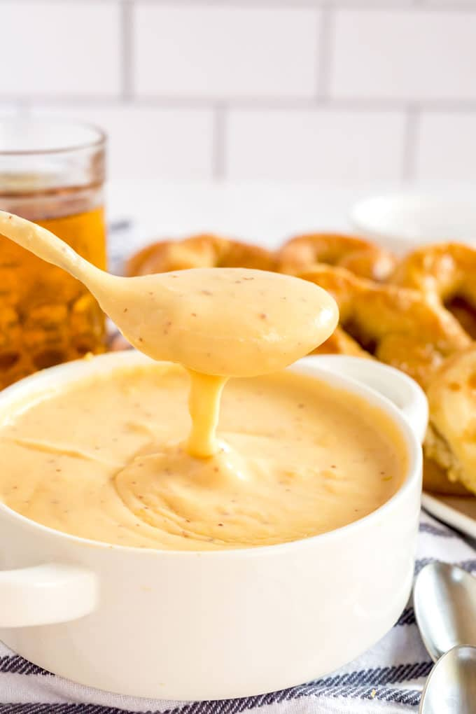 scooping cheese dip from a white bowl.