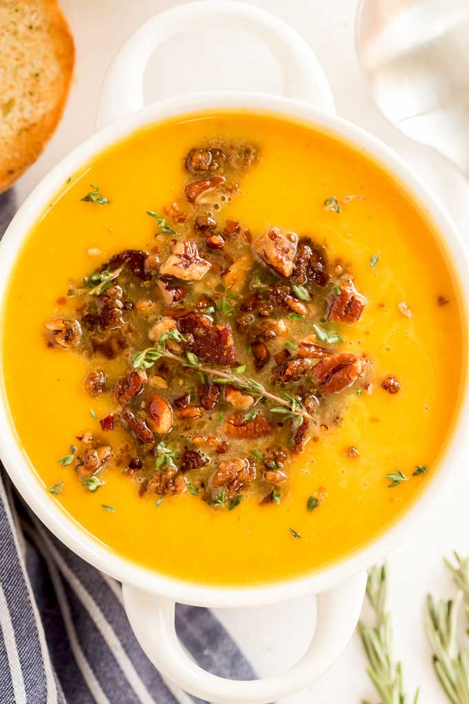 Top view of a white bowl filled with butternut squash soup and topped with a crispy bacon pecan topping