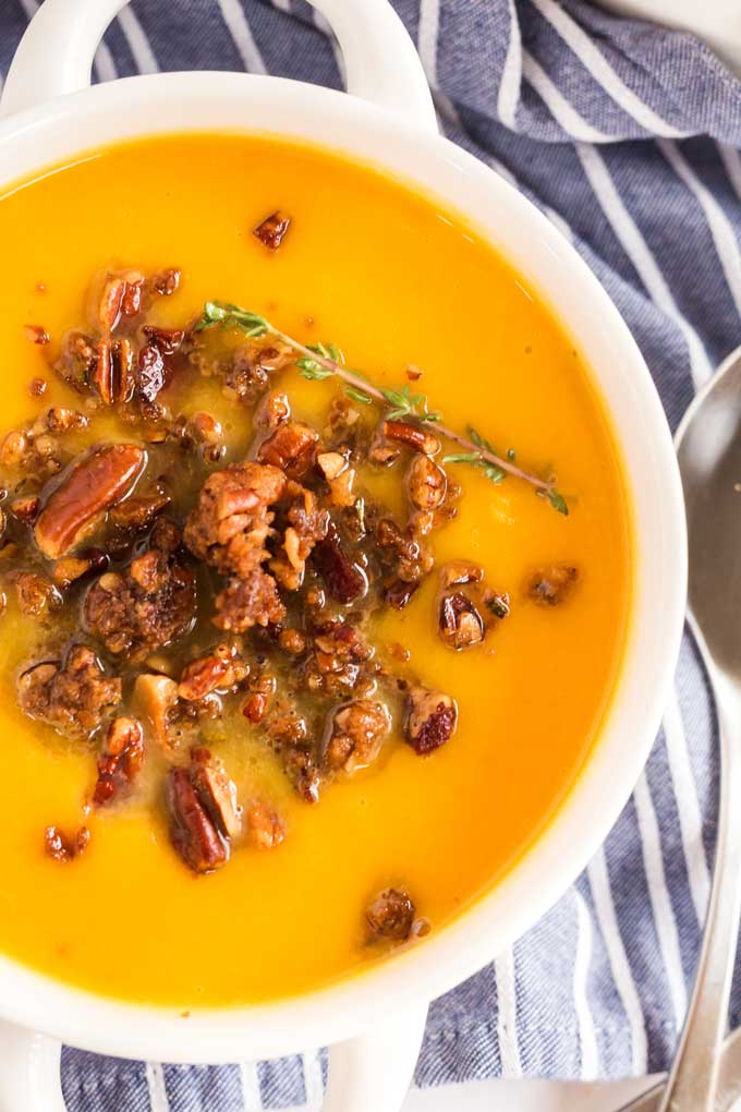 Close up top view of a white bowl filled with butternut squash soup and topped with a bacon-pecan topping.