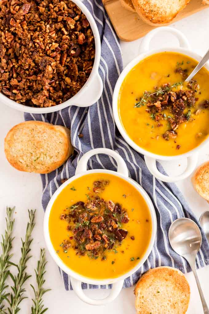Bowls of butternut squash soup with pecan abcon topping on a white marble surface.
