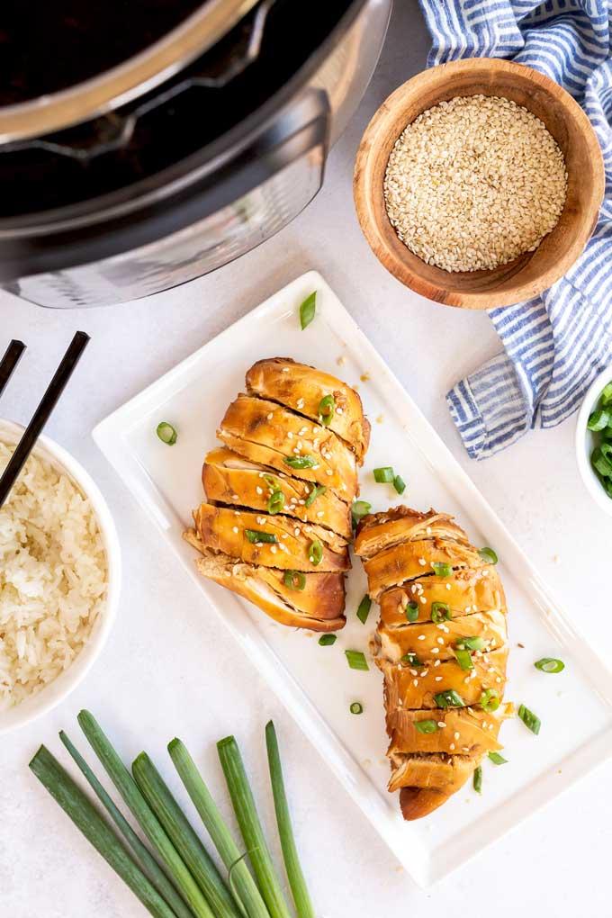 Sliced boneless chicken breast in teriyaki sauce on a white plate.