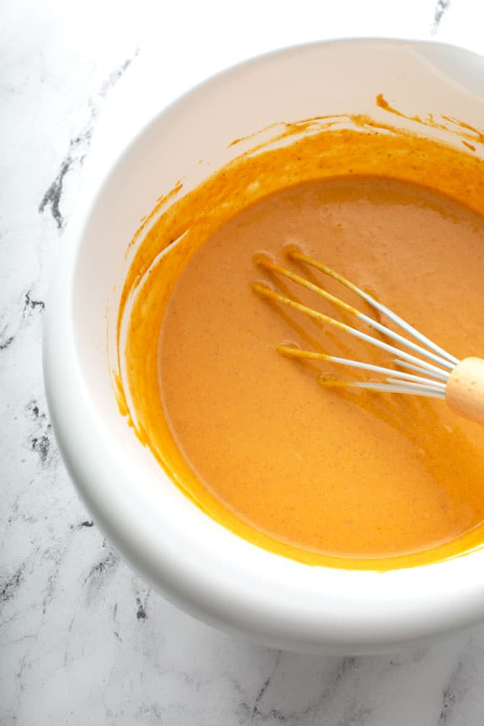 Smooth pumpkin pie filling in a white bowl.