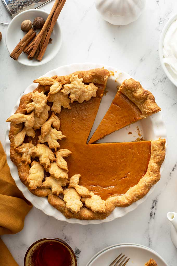 Top view of a pumpkin pie with a few slices cut.