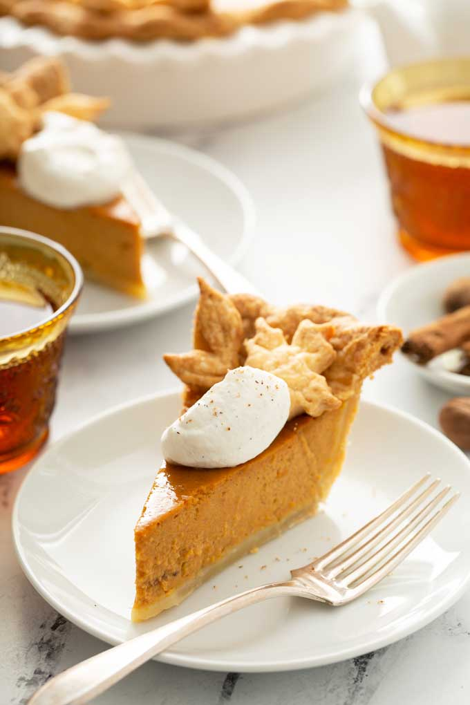 Slice of pumpkin pie topped with maple whipped cream on a white plate.