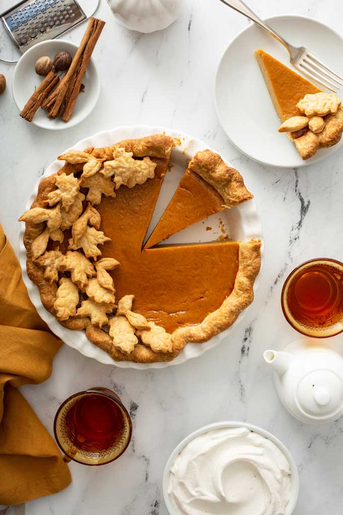 Top view of a full pie decorated with fall pastry leaves.