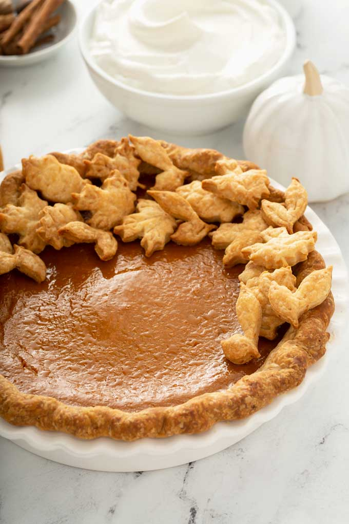 A whole pie decorated with pastry fall leaves on a pie plate.