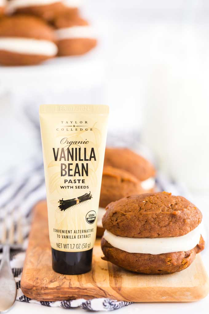 Whoopie cookie next to a vanilla bean container.