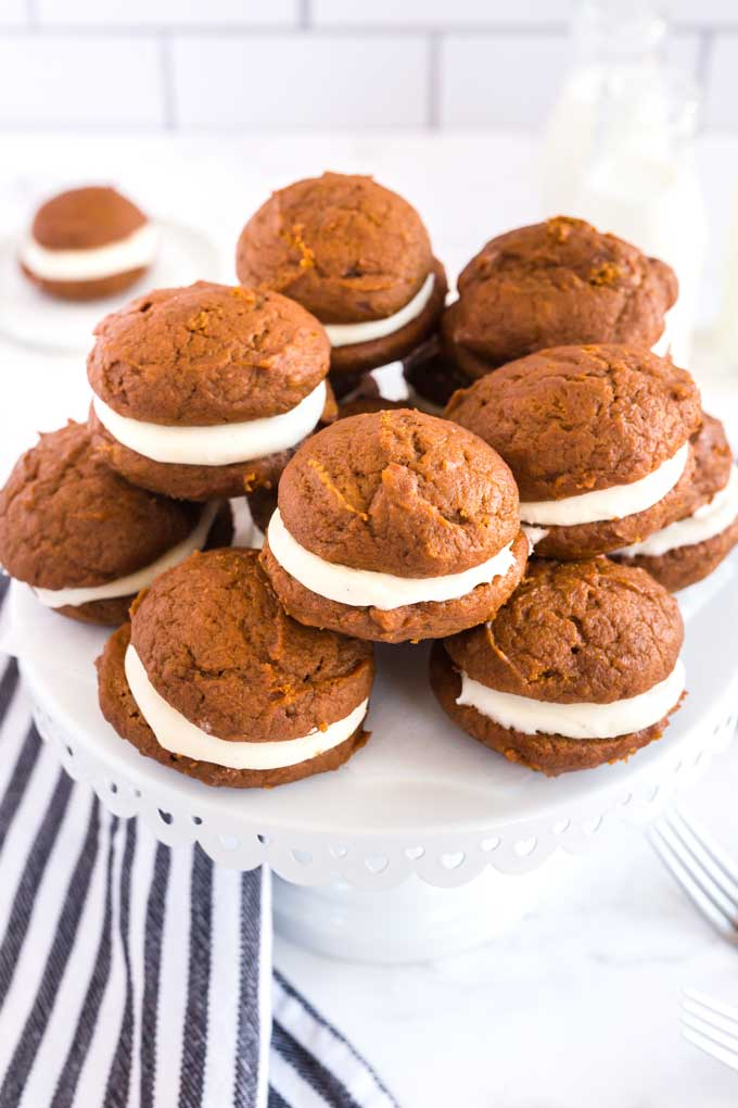 A group of homemade whoopie cookies on a cake platter.