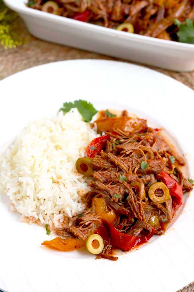 Ropa vieja cuban beef stew served with rice on a white plate.