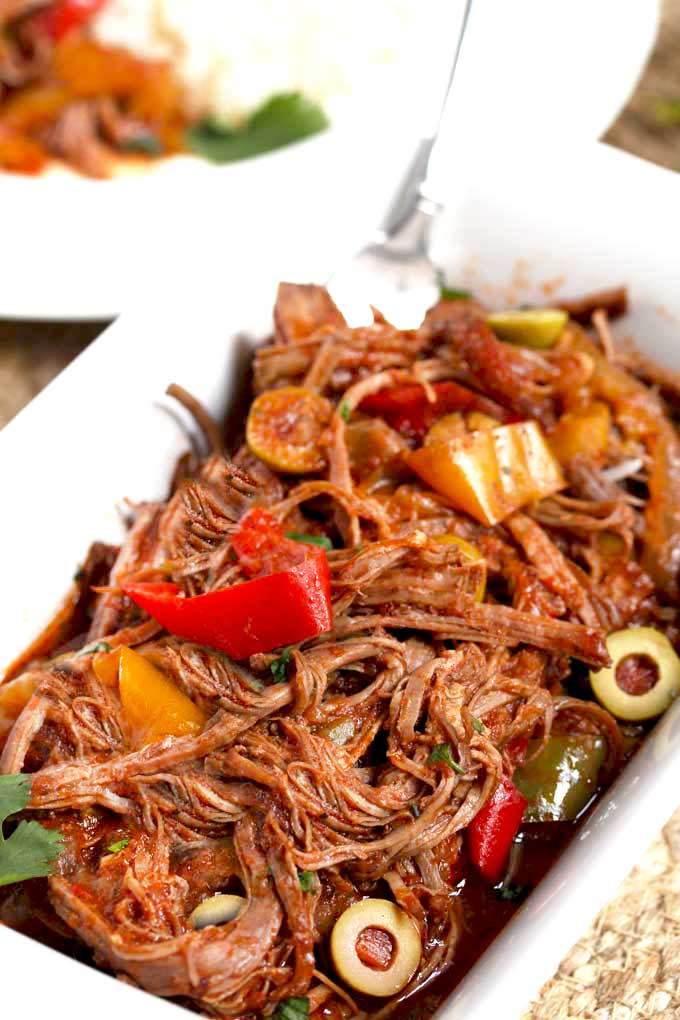 Shredded beef Cuban Ropa Vieja in a white serving dish.