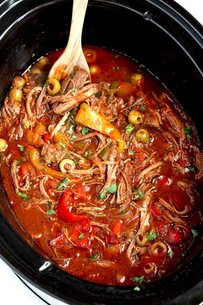 Shreds of beef with bell peppers, onions and olives simmering in a crock pot.