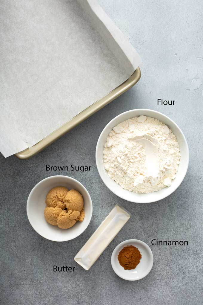 Ingredients to make the shortbread layer on a gray surface.