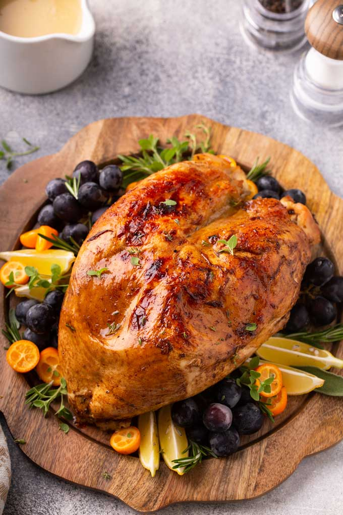 Golden brown turkey breast on a wooden tray garnished with fruit and herbs