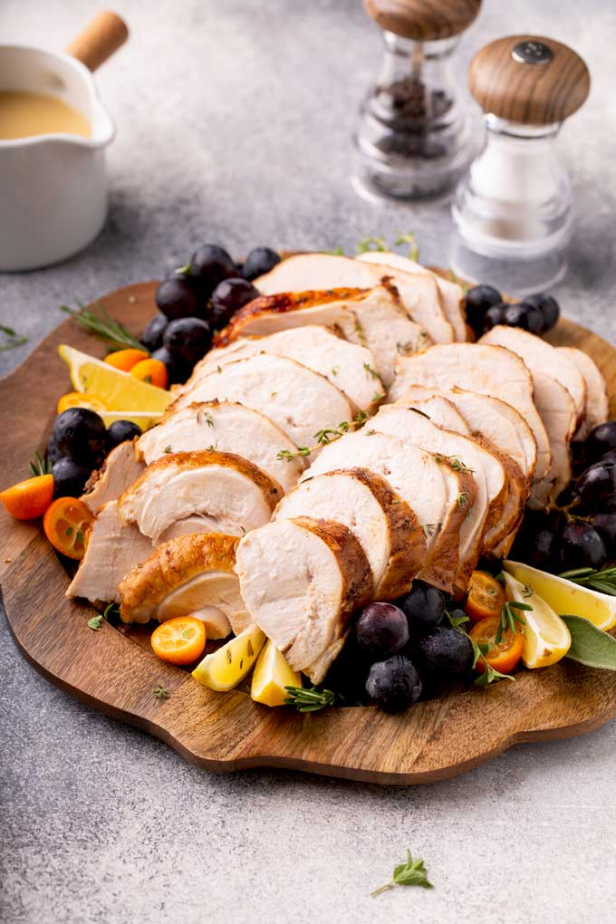 Sliced turkey breast and a small gravy pitcher on a grayish surface.