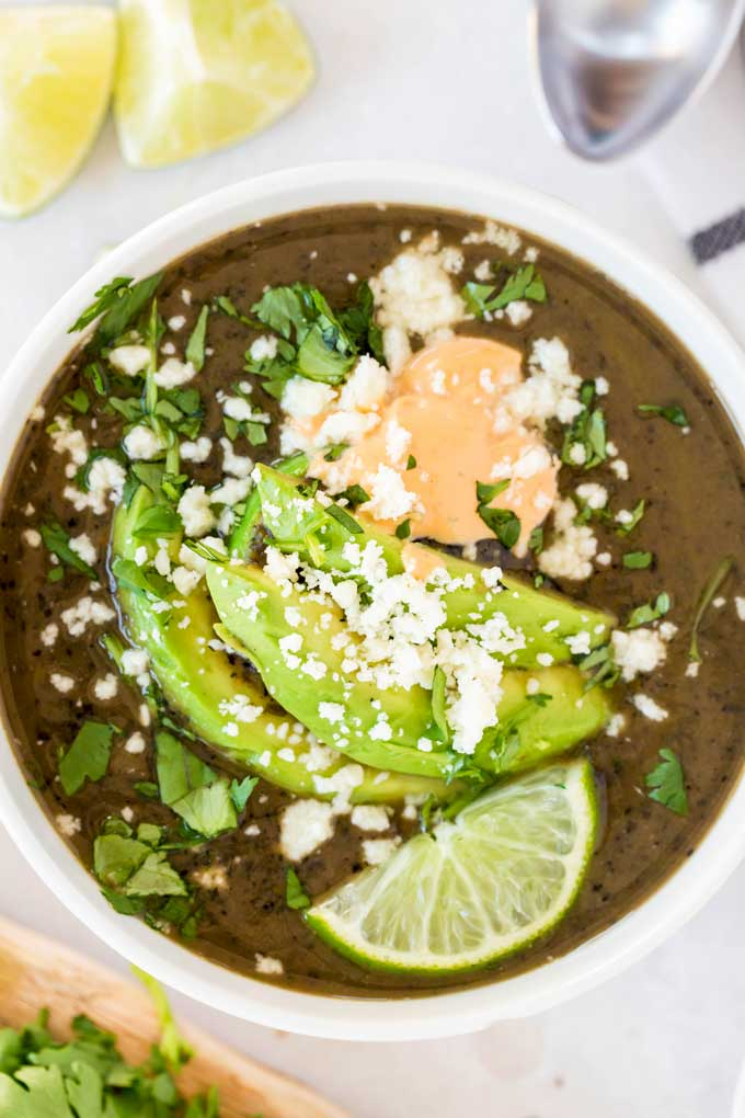 Top view of a white bowl filled with creamy black bean soup with toppings.