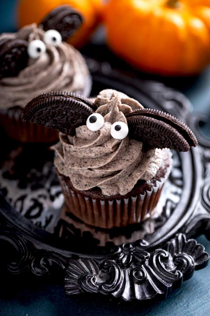 Oreo cupcake with cookies and cream frosting decorated with oreo cookies and candy eyes to resemble a bat.