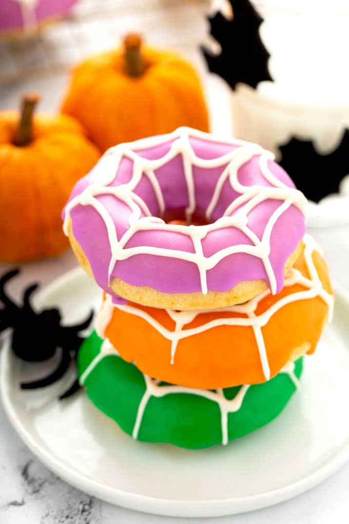 A trio of baked donuts glazed in Halloween colors with white chocolate cobwebs.
