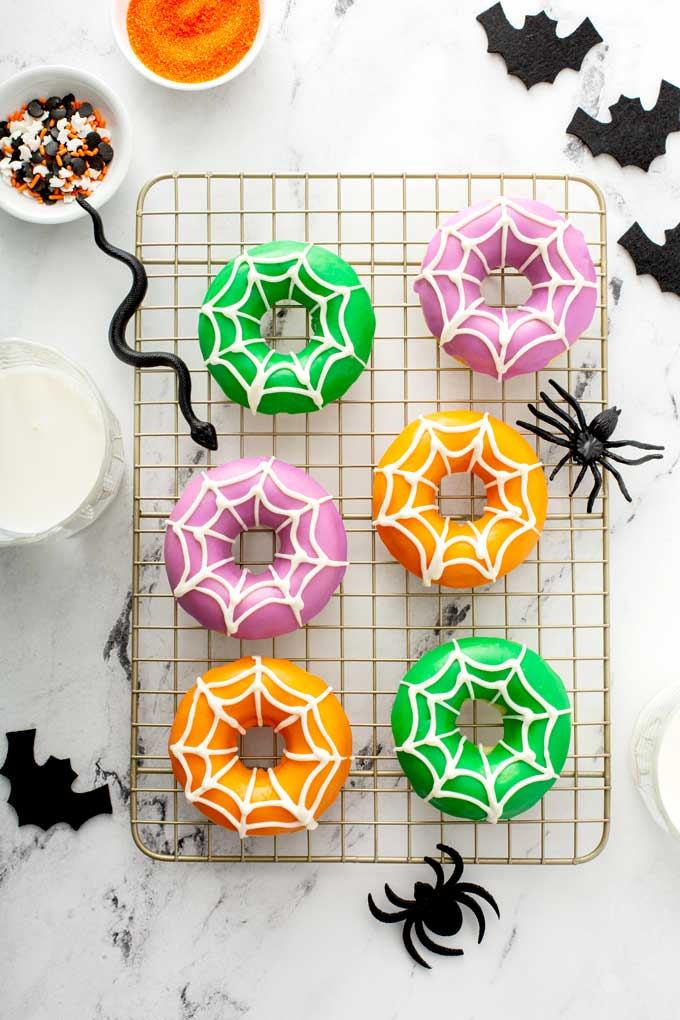 Decorated donuts on a wire rack.