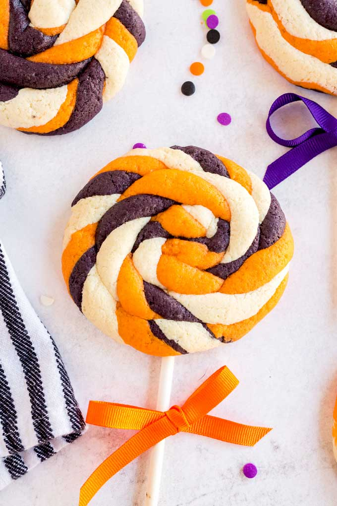 White, orange and black lollipop cookies on a white surface