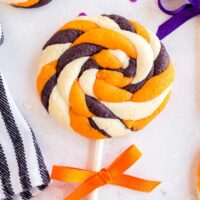 Pin image of a halloween white, orange and black cookie in a lollipop shape