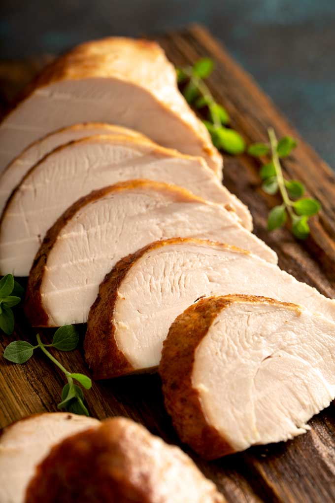 Slices of roasted turkey breast on a wooden cutting board