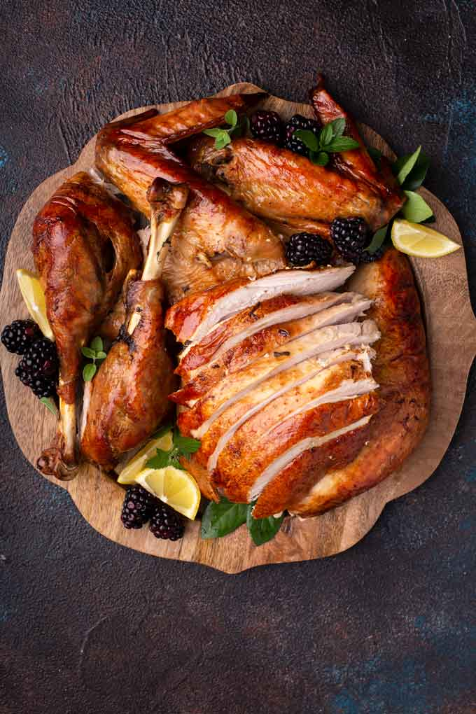 Carved juicy roast turkey and sliced turkey breast meat on a wooden serving tray.