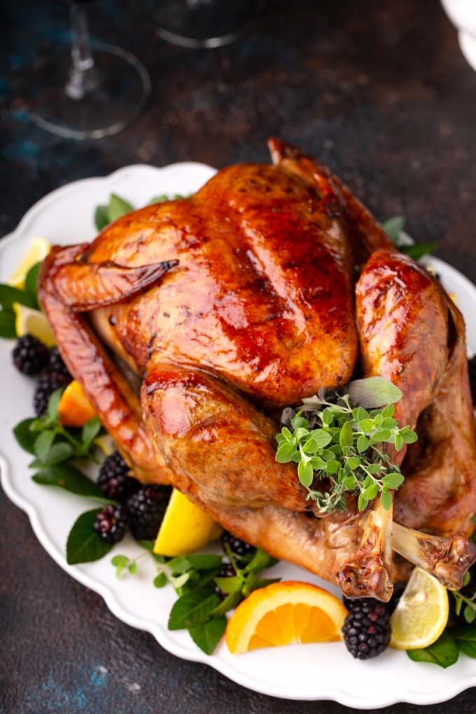 Golden brown turkey on a serving platter garnished with citrus, herbs and fruit.