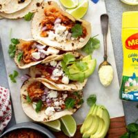 Tacos of chicken tinga with toppings on a white board
