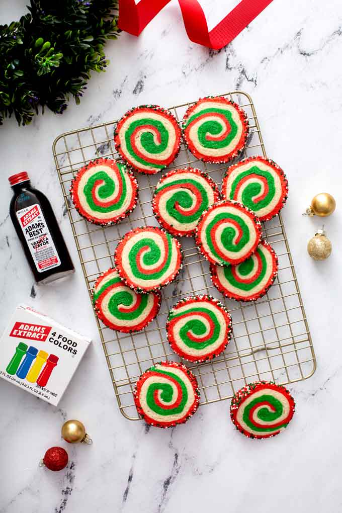 Festive cookies on a cooling rack next to a bottle of vanilla extract and a box of food coloring