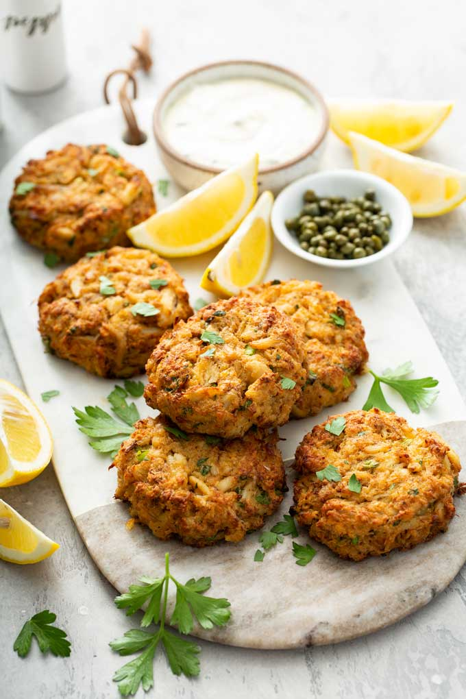 Crab cakes on a white marbled board with a bowl of lemon aioli and capers.