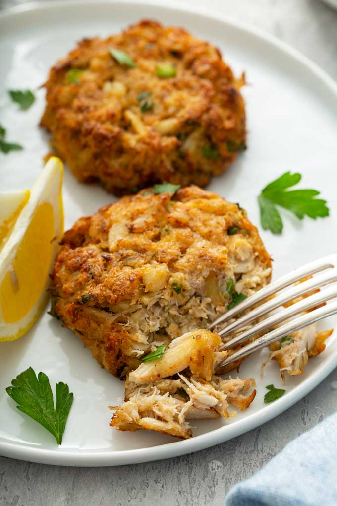 Fork flaking a golden brown crab patty