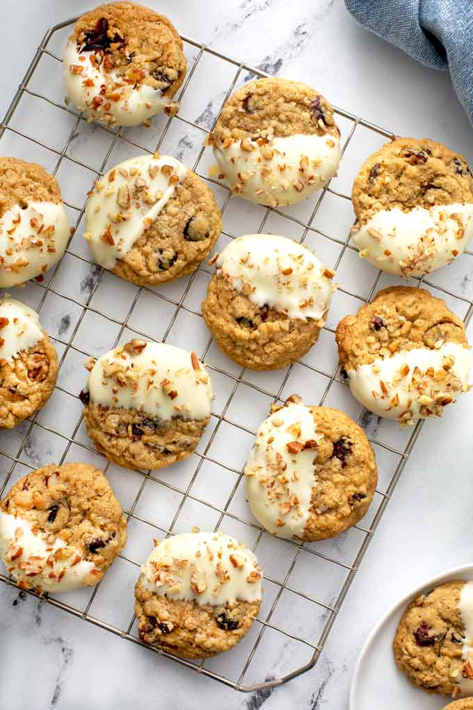 Cranberry Oatmeal Cookies dipped in white chocolate on a cooling rack