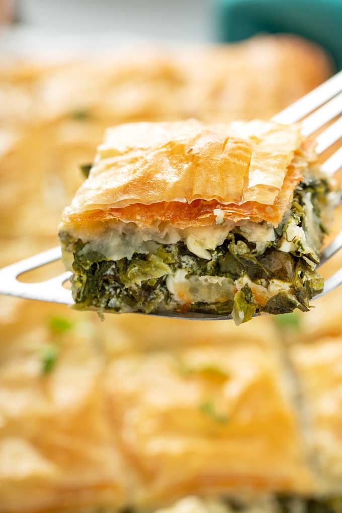 A piece of spanakopita lifted with a spatula.