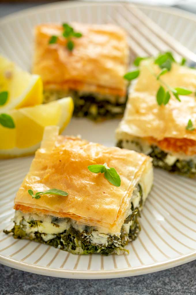 Spinach and feta cheese pie cut into squares on a serving plate