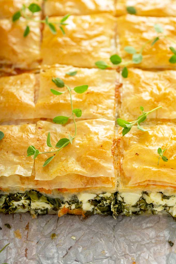 Golden brown spanakopita scored into square pieces.