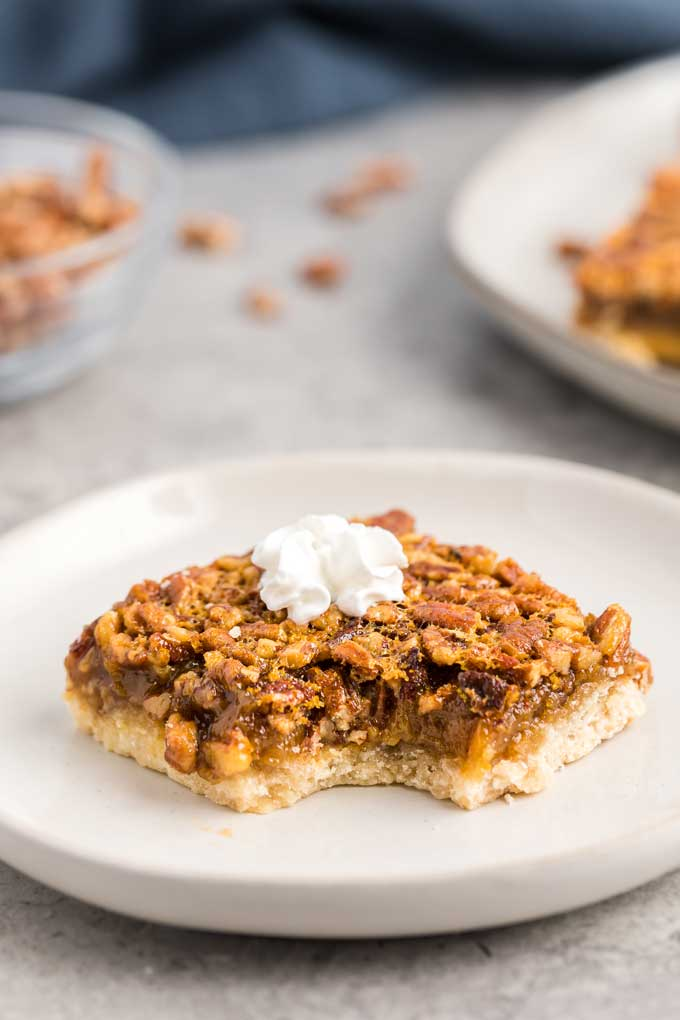 A piece of pecan pie bar with a bite taken off on a plate tooped with whipped cream